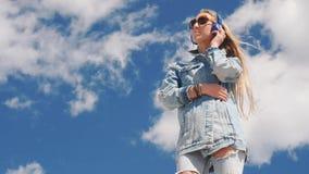La mujer joven en gafas de sol y los vaqueros llevan música que escucha con los auriculares al aire libre almacen de video