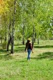 La mujer joven en la guirnalda de dientes de león camina entre los árboles de abedul, visión desde la parte posterior Foto de archivo
