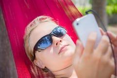 La mujer joven en hamaca debajo de las palmeras en la playa del océano escucha MU Fotografía de archivo