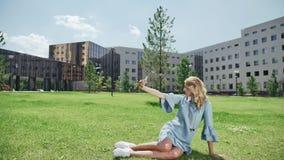 La mujer joven en hierba verde con smartphone toma las imágenes, selfie almacen de video