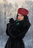 La mujer joven en invierno arropa en el parque Fotografía de archivo