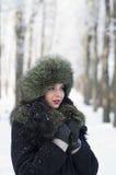 La mujer joven en invierno arropa en el parque Foto de archivo