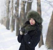 La mujer joven en invierno arropa en el parque Fotos de archivo libres de regalías
