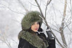 La mujer joven en invierno arropa en el parque Imagenes de archivo