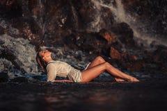 La mujer joven en la camisa y el bikini blancos miente en roca cerca de waterfal Fotografía de archivo