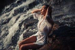 La mujer joven en la camisa y el bikini blancos se sienta en roca cerca de waterfal Imagen de archivo