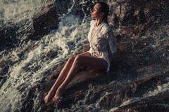 La mujer joven en la camisa y el bikini blancos se sienta en roca en corriente Fotos de archivo libres de regalías