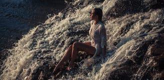 La mujer joven en la camisa y el bikini blancos se sienta en roca en corriente Fotografía de archivo