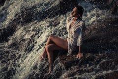 La mujer joven en la camisa y el bikini blancos se sienta en roca en corriente Imagen de archivo libre de regalías