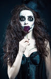 La mujer joven en la imagen del payaso anormal gótico triste sostiene la flor marchitada Foto de archivo libre de regalías