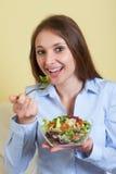 La mujer joven en la sala de estar ama la ensalada fresca Fotos de archivo