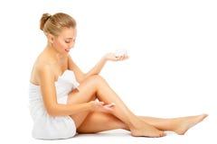 La mujer joven en la toalla terry pone la crema en las piernas Fotografía de archivo