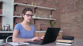 La mujer joven en lentes escribe notas en tablero durante el trabajo o estudiar en línea en ordenador portátil en casa almacen de video