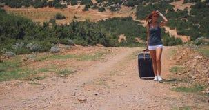 La mujer joven en los pantalones cortos blancos va solamente a lo largo de la trayectoria con equipaje almacen de video