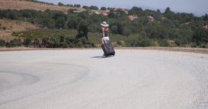 La mujer joven en los pantalones cortos blancos va solamente a lo largo del camino con equipaje metrajes