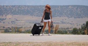 La mujer joven en los pantalones cortos blancos va solamente a lo largo del camino con la maleta metrajes