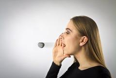 La mujer joven en negro est? gritando en algo griter?o La palabra le gusta una piedra foto de archivo libre de regalías