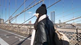 La mujer joven en Nueva York camina sobre el puente de Brooklyn en un día soleado almacen de metraje de vídeo