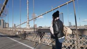 La mujer joven en Nueva York camina sobre el puente de Brooklyn en un día soleado almacen de video