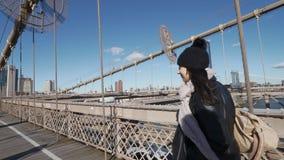 La mujer joven en Nueva York camina sobre el puente de Brooklyn en un día soleado metrajes