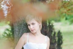 La mujer joven en parque cerca de un árbol Imágenes de archivo libres de regalías