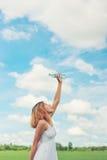 La mujer joven en parque vierte el agua sobre una cara para freshing en los gras Fotografía de archivo libre de regalías