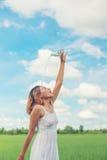 La mujer joven en parque vierte sobre una cara para freshing en el prado Fotografía de archivo
