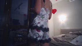 La mujer joven en pijamas viene a la ventana panorámica en dormitorio con la taza de té Balones de aire Noche oscura almacen de metraje de vídeo