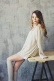 La mujer joven en rebeca hecha punto y los calcetines calientes despiertan por la mañana en dormitorio escandinavo acogedor y sen Fotografía de archivo libre de regalías