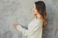 La mujer joven en rebeca hecha punto y los calcetines calientes despiertan por la mañana en dormitorio escandinavo acogedor y sen Fotos de archivo libres de regalías
