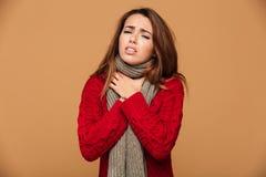 La mujer joven en rojo hizo punto el suéter con sostenerse de los síntomas de la angina fotos de archivo