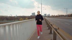 La mujer joven en ropa de deportes está corriendo en un puente en el fondo de la ciudad almacen de video