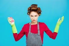 La mujer joven en rosa presenta con los guantes de goma Imagen de archivo