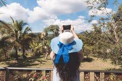 La mujer joven en sombrero hace la fotografía de la terraza tropical de Forest Landscape From Balcony Or fotos de archivo