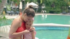 La mujer joven en traje de baño abraza al niño con el arco púrpura en la cabeza metrajes