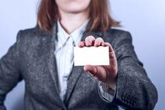 La mujer joven en traje gris sostiene la tarjeta de visita Fotos de archivo