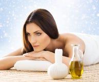La mujer joven en un balneario detrás da masajes a procedimiento Imagenes de archivo