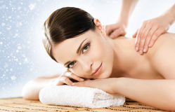 La mujer joven en un balneario detrás da masajes a procedimiento Fotografía de archivo