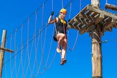 La mujer joven en un casco con seguro en un parque que sube de la aventura camina por un simulador de la cuerda contra un cielo a Imagenes de archivo