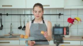 La mujer joven en un delantal gris lleva un blog culinario, tiroteo video almacen de video