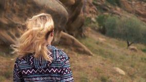 La mujer joven en un inconformista alegre que el suéter púrpura está caminando en las montañas, la señora está caminando en Georg almacen de video