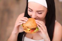 La mujer joven en un restaurante de cena fino come una hamburguesa, ella se comporta incorrectamente Foto de archivo libre de regalías