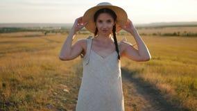 La mujer joven en un sombrero se coloca en el campo durante la puesta del sol almacen de video