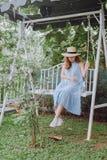La mujer joven en un sombrero se sienta en un oscilación Imagen de archivo libre de regalías