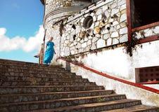 La mujer joven en un vestido azul largo viene abajo a lo largo de una pared de la casa antigua Foto de archivo libre de regalías