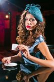La mujer joven en un vestido de la turquesa se sienta en un club nocturno y un café de las bebidas imágenes de archivo libres de regalías