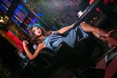 La mujer joven en un vestido de la turquesa se sienta en un club nocturno y un café de las bebidas fotos de archivo libres de regalías