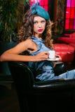 La mujer joven en un vestido de la turquesa se sienta en un club nocturno y un café de las bebidas imagenes de archivo