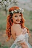 La mujer joven en un vestido lujoso es permanente y sonriente en un jardín floreciente Fotos de archivo libres de regalías