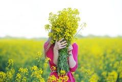 La mujer joven en un vestido rojo ha ocultado una cara detrás de un ramo de colores amarillos imágenes de archivo libres de regalías